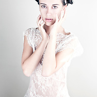 Young girl with brunette hair wearing white lace party dress looking down with hands to face