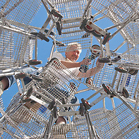 "Artist Anthony Schmitt, 53, works atop the 14th Annual 'Edgemar Holiday Tree' on Monday, November 22, 2010. This years art sculpture/installation is titled, ""The Courage Tree."" It is 33 feet tall and is constructed from 84 shopping carts. No scaffolding was used to erect the sculpture, it served as its own scaffolding. Schmitt uses shopping carts because they are a symbol both of abundance and a reminder of those less fortunate."
