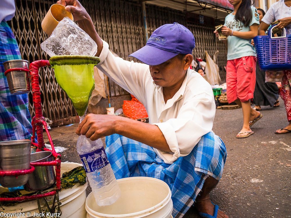 16 JUNE 2013 - YANGON, MYANMAR: A water vendor in Yangon. He refills plastic water bottles by running tap water over a block of ice. Yangon, formerly Rangoon, is the largest city in Myanmar. It is the former capital of the Southeast Asian country. It's still Myanmar's economic capital.      PHOTO BY JACK KURTZ