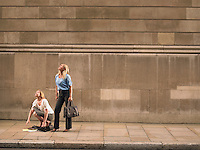 Two women on sidewalk looking up