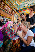 Kamari Gurung engages with Rosa Hollows after surgery. Ruth and Rosa Hollows at Pullarhari Monestry for the outreach micro surgical eye camp held on the outsirks of the Kathmandu Valley 2014. Rosa greets Kamari Gurung 80 from Haibung Village after patches are removed.