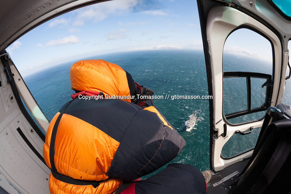 A man photographing Gorch Foch, a german navy training ship, from an helicopter, sailing at Faxaflói while leaving Iceland after an visit.