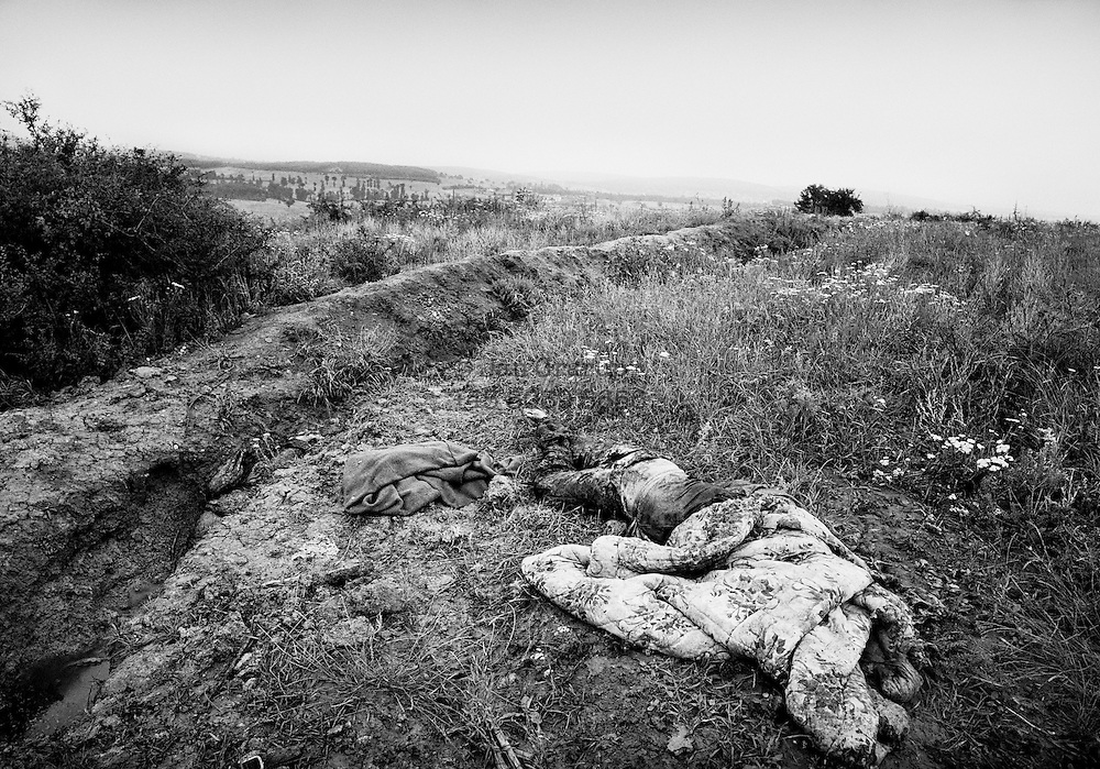 Covered body in an old trench in central Kosovo.  Spring 1999.