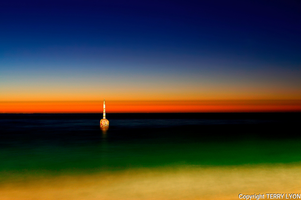 The metal tip of the iconic Cottesloe pylon shines like gold reflecting the last rays of the setting sun, with a rainbow of colors starting from the yellow sand in the shallow waters edge through green to blue water onto the yellow orange and red horizon to the sky with shades of light to dark blue. Signed Limited Edition #7/50 available