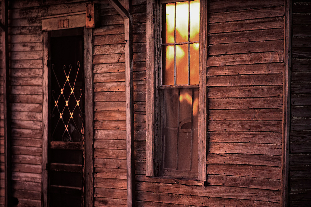 The textures of this old Texas house with unpainted wooden slats and window next to the railroad crossing are lit by the setting sun.