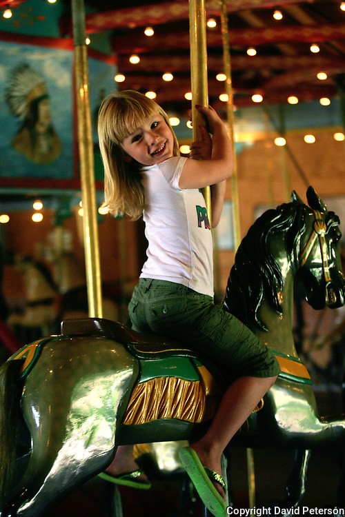 Kaitlyn Hove, 6, enjoys her ride on the Herschell-Spillman Carousel in Story City, Iowa.  One of a vanishing species, this machine was built in 1913 by  the Herschell-Spillman Company of Tonowanda, New York.  It was originally owned by T.P. Gifford of Grundy Center, Iowa, who traveled the Iowa countryside, taking the carousel to county fairs and town celebrations.  ..In 1980, interest in the old merry-go-round was resurrected and restoration began.  After eighteen months, the original stencils, colors and paints were completely restored to their present gleaming condition...The splendid wooden figures were hand-carved from poplar and include twenty horses, two roosters, two pigs, two dogs, two chariots and a whirling tub.  Calliope tunes are generated by a 1936 Wurlitzer Military Band organ housed in the center of the carousel.  photo by David Peterson