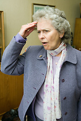 Older woman holding a hand to her head looking confused,
