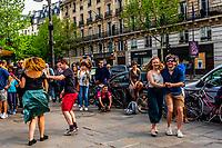 Two couples dancing on the sidewalk on Boulevard St. Germain des Pres, Latin Quarter, Paris, France.