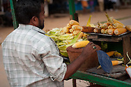 A street vendor fanning the fire to cook and sell corn on the cob in Bangalore, India.