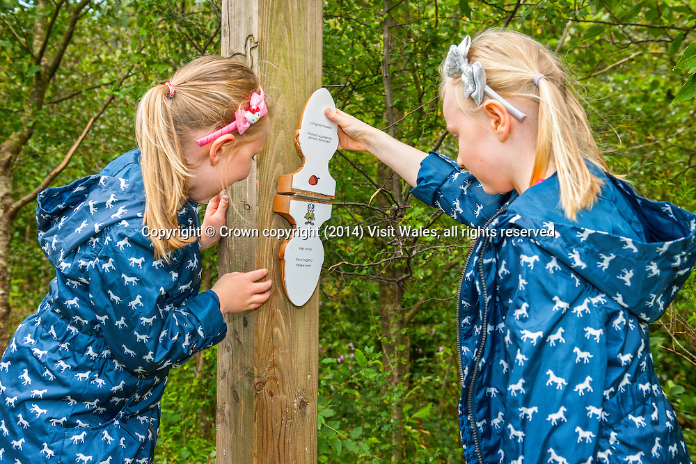 Two girls looking at sign on interactive trail around one of lakes at Glyncorrwg<br /> Afan Forest Park <br /> Neath Port Talbot<br /> Valleys<br /> South<br /> People<br /> Lifestyle