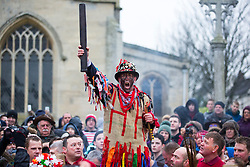 © Licensed to London News Pictures. 06/01/2017. Haxey UK. The Fool (Dale Smith) start's the Haxey Hood game in the village of Haxey in Lincolnshire. The game of Haxey Hood dates back to the 14th century. It is said that Lady de Mowbray was riding towards the village of Haxey, north Lincolnshire, when her silk riding hood was blown away by the wind. Farm workers in a nearby field rushed to help and chased the hood, when it was eventually caught by one of the men. He was too shy to return it to the lady so handed it to another worker, who gave it to her. She thanked the man who had returned the hood and said he had acted like a lord, whereas the worker who caught the hood was a fool. The act of chivalry and resulting chase amused her so much she donated 13 acres of land on condition the chase for the hood was reenacted each year. Photo credit: Andrew McCaren/LNP