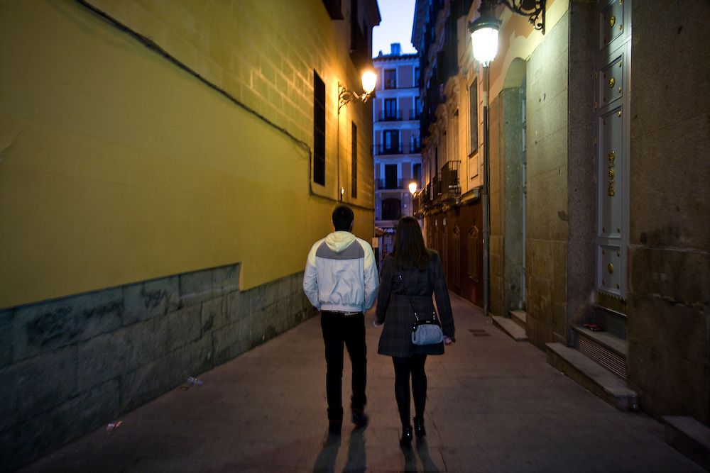 "7:00 AM: Iván Massa, 26, and María Padín, 25, walk together after a ""churros con chocolate"" brealfast at San Ginés, having enjoyed a long party night out in Madrid."