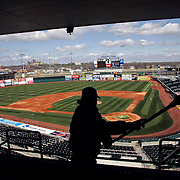 On the eve of opening day, 2007, an Iowa Cubs worker was busy sweeping away dust that had collected on the windows of the sky boxes at Principal Park in Des Moines, Iowa.  The stadium was being spruced up for the game between the Cubs and Round Rock.   Des Moines has had a AAA baseball team for over 30 years, with this year's club being the affiliate of the Chicago Cubs.