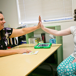 Special Education teacher Mary Staley (left) gives a high five to autistic student Meredith Bacon (right, age 12) after she correctly identified the main idea of a story during a structured learning class at Hillside Junior High School in Boise, Idaho. Thursday September 3, 2015
