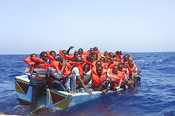 May 20, 2017 - Lampedusa, Sicily, Italy - LAMPEDUSA, ITALY - MAY 20: Refugees and migrants are seen floating in an overcrowded wooden boat as they wait to be assisted by search and rescue crew members from NGO Sea-Eye on May 20, 2017 in international waters off the coast of Libya. (Credit Image: © Christian Marquardt/NurPhoto via ZUMA Press)