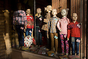 Mannequins in the window of a clothing business displaying childrens' western-style clothes in modern Luxor, Nile Valley, Egypt.