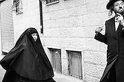 A husband and wife walk the more modern part of Me'a She'arim Street in Jerusalem. The multi-layered gawn worned by the woman in this image is a symbol of her decendance from a newsest current called the Haredi Burka sect, a new group of orthodox Jews from Mea Shearimg who have Sephardi or Mizrahi origins and who may or may not cover their faces with a black vail as well as their entire bodies with 'tent-like garmeth.'