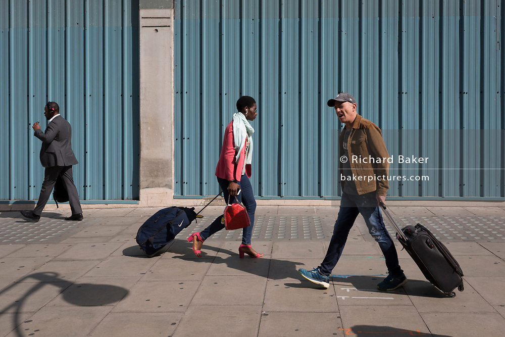 Passers-by walk in different directions while both pulling wheelies bags on Oxford Street, on 5th June 2019, in London, England.