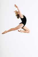 Gymnast (16-17) leaping in air side view