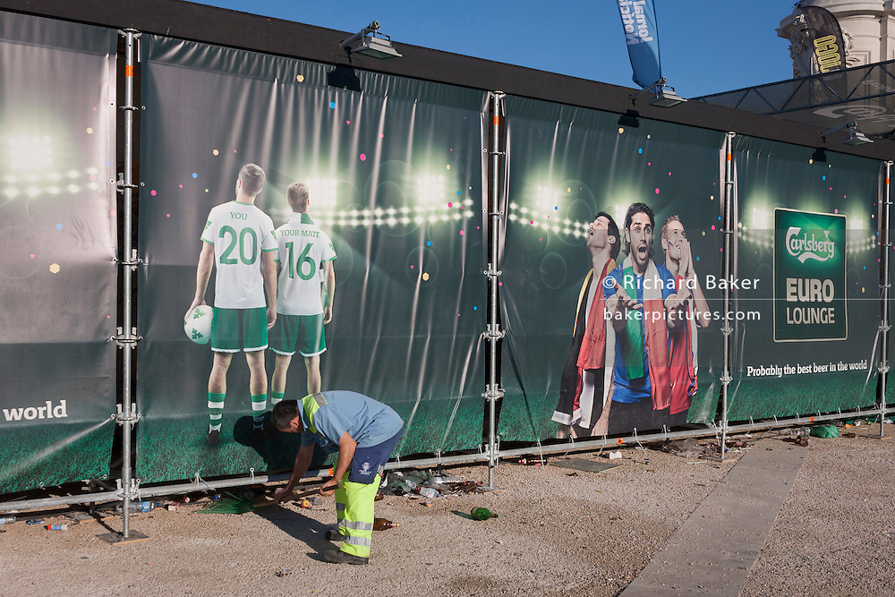 A city worker sweeps litter from under Carlsberg advertising in Lisbon's Praca do Commercio the morning after Portugal's victory over France in the Euro 2016 tournament final.