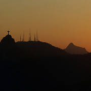 The iconic Cristo Redentor, Christ the Redeemer statue at sunset atop the mountain Corcovado shot from Sugar Loaf Mountain. The Christ statue was voted one of the seven wonders of the modern world in 2007. It was designed by Brazilian Heitor de Silva Costa and was inaugurated in 1931 having taken years to assemble. Rio de Janeiro, Brazil. 24th August 2010. Photo Tim Clayton..