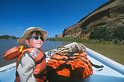 5-year old boy riding in dory on O.A.R.S. outfitters trip on the San Juan River in Utah.