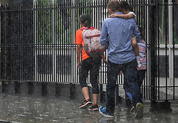 © Licensed to London News Pictures. 11/07/2017. London, UK. A family run for cover as a sudden burst of heavy rain catches people out in central London. Photo credit: Peter Macdiarmid/LNP