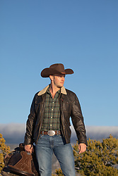 cowboy with a saddle on a mountain