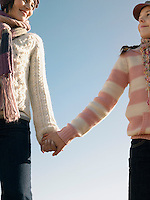 Mother and daughter holding hands outdoors low angle view cropped
