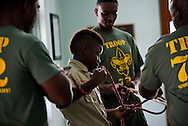 Boy Scout Troop 772 member Antonio Green (center) practices the clove-hitch knot, as volunteers with the St. Lucie County Fire District, Remi Dieujuste (left) and Duane Fenn (right), along with registered nurse Kamron Pratt (center), guide him during the troop's first meeting after the start of the school year at the Fort Pierce Police Department Willie B. Ellis Police Substation on Avenue D in Fort Pierce on Aug. 20, 2014. (XAVIER MASCAREÑAS/TREASURE COAST NEWSPAPERS)