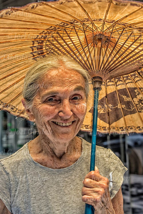 Smiling  Lenorel Wesely, 85 years old walking holding Japanese umbella protecting her from the rays of  the noon sun  and providing shade.