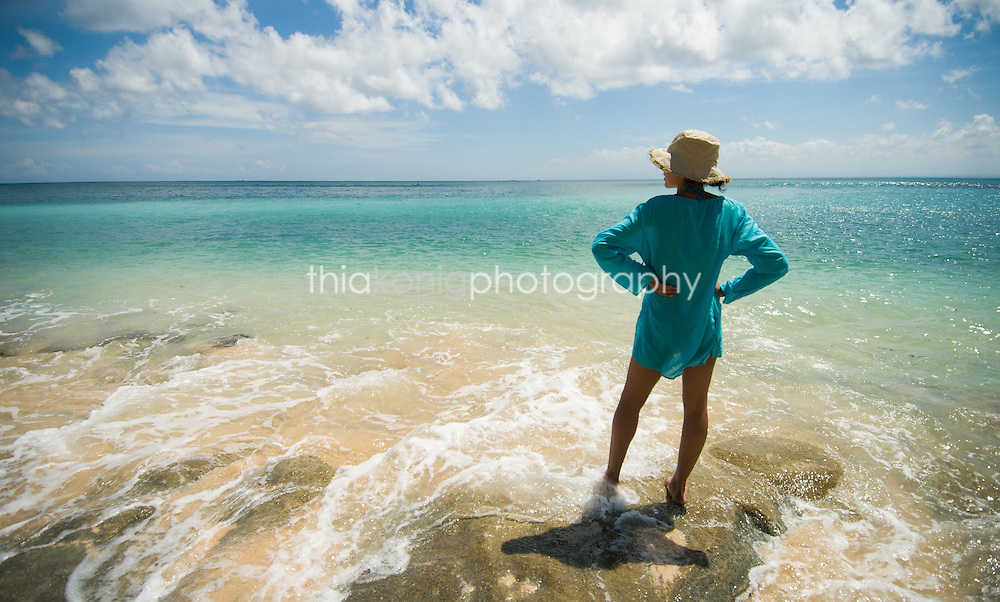Woman in blue sun shirt stands in the shallow waves with hands on hip, Bali