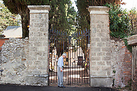 """AFFILE, ITALY - 23 AUGUST 2012: Sante Mosetti, member of the Cultural Association Marshall Rodolfo Graziani, closes the gate of the cemetery where the fascist marsahll was buried, in Affile, a town with a population of 1,600 80km east of Rome, on August 23, 2012. A mausoleum and park, dedicated to the memory of Fascist Field Marshall Rodolfo Graziani, has recently been opened in the Italian town of Affile. At a cost of €127,000 to local taxpayers, the mayor Ercole Viri has expressed hope that the site will become as 'famous and as popular as Predappio' – the burial place of Mussolini which has become a shrine to neo-Fascists. Rodolfo Graziani was the youngest colonel in the Regio Esercito (Royal Italian Army), known as the """"Butcher of Fezzan"""" and the """"Butcher of Ethiopia"""" for the brutal military campaigns and gas attacks he led in Libya and Ethiopia under the dictatorship of Benito Mussolini under which he then became Minister of Defence from 1943 to 1945."""