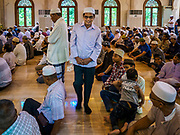 25 JUNE 2017 - BANGKOK, THAILAND: A man walks to where his friends are sitting in Ton Son Mosque before Eid al-Fitr services. Eid al-Fitr is also called Feast of Breaking the Fast, the Sugar Feast, Bayram (Bajram), the Sweet Festival or Hari Raya Puasa and the Lesser Eid. It is an important Muslim religious holiday that marks the end of Ramadan, the Islamic holy month of fasting. Muslims are not allowed to fast on Eid. The holiday celebrates the conclusion of the 29 or 30 days of dawn-to-sunset fasting Muslims do during the month of Ramadan. Islam is the second largest religion in Thailand. Government sources say about 5% of Thais are Muslim, many in the Muslim community say the number is closer to 10%.    PHOTO BY JACK KURTZ