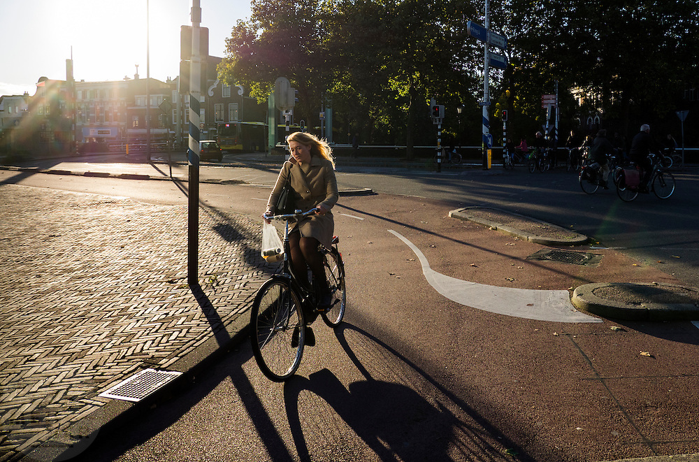 Een vrouw fietst met een paar boodschappen in een plastic tasje langs het Ledig Erf in Utrecht.<br /> <br /> A woman cycles with some groceries in a plastic bag near Ledig Erf in Utrecht.