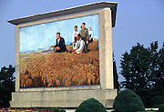 Propaganda billboard showing the 'Great Leader' Kim Il Sung and a bountiful harvest.