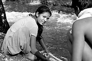 A girl washes her family clothes on a riverbank.