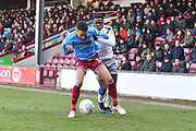 Scunthorpe United player James Perch (14) and Colchester United player Kwame Poku(49) during the EFL Sky Bet League 2 match between Scunthorpe United and Colchester United at Glanford Park, Scunthorpe, England on 14 December 2019.