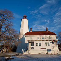 "The Sandy Hook Lighthouse, located about one and a half statute miles (2.4 km) inland from the tip of Sandy Hook, New Jersey, is the oldest working lighthouse in the United States. It was designed and built in 1764 by Isaac Conro.The light was built to aid mariners entering the southern end of the New York harbor. It was originally called New York Lighthouse because it was funded through a New York Assembly lottery and a tax on all ships entering the Port of New York. Sandy Hook Light has endured an attempt to destroy it (as an aid to British navigation) by artillery Captain Alexander Hamilton,[citation needed] and a subsequent occupancy of British soldiers during the Revolutionary War. Perhaps most impressively, it has endured exposure to the elements on the end of Sandy Hook. The view of the New York skyline from the bridge crossing into ""the Hook"" illustrates the importance this light played in the history of New York harbor. During the summer weekends, the New Jersey Lighthouse Society offers free tours every half hour from 12:00 p.m. until 4:30 p.m.When the lighthouse was built in 1764, it stood only 500 feet (150 m) from the tip of Sandy Hook; however, today, due to growth caused by littoral drift, it is almost one and half miles (2.4 km) inland from the tip. Sandy Hook Lighthouse is part of the Sandy Hook Unit of Gateway National Recreation Area. The Sandy Hook Lighthouse was restored in spring 2000."