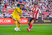 Luke O'Neill (#2) of AFC Wimbledon takes on Chris Maguire (#7) of Sunderland AFC during the EFL Sky Bet League 1 match between Sunderland and AFC Wimbledon at the Stadium Of Light, Sunderland, England on 24 August 2019.
