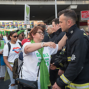 People shacking hand with the firemen at the Grenfell Silent Walk - 1 Year On to mark the anniversary of the Grenfell Tower fire, demand Justice for Grenfell on June 14, 2018, London, UK.