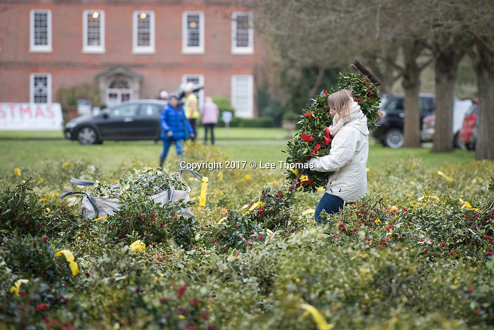 Burford House Garden Stores, Tenbury Wells, Worcestershire, UK. 5th December 2017. Buyers flock to Burford House in Tenbury Wells to take part in the annual mistletoe, wreaths, holly and Christmas tree auctions. Pictured: A young woman carries a holly wreaths in the grounds of Burford House. // Lee Thomas, Tel. 07784142973. Email: leepthomas@gmail.com  www.leept.co.uk (0000635435)