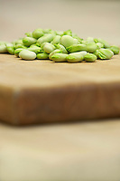 Fresh broad beans on wooden board close-up