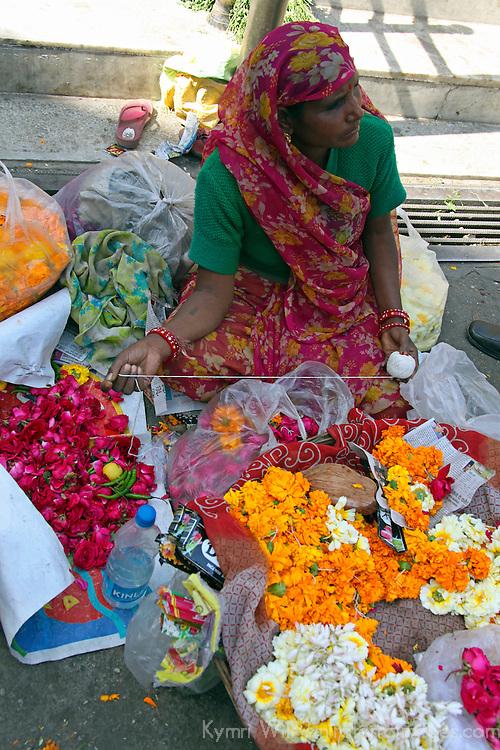 Asia, India, Udaipur. Woman selling flowers for offering outside temple in Udaipur.