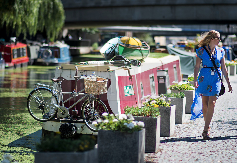 © Licensed to London News Pictures. 02/08/2018. London, UK. A woman walks along the canal towpath at Paddington  in London in the mid day sunshine. Another heatwave is expected to hit parts of the UK with record temperatures expected in parts of Europe. Photo credit: Ben Cawthra/LNP