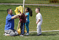 Middletown, New York - A coach helps a child put on a pinnie during a soccer program at the Middletown YMCA on April 14, 2012.