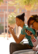 A young man on a texting on a college campus.