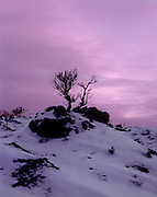 AA00875-03...NORTH DAKOTA - Sunset over snow covered red scoria in North Unit of Theodore Roosevelt National Park.