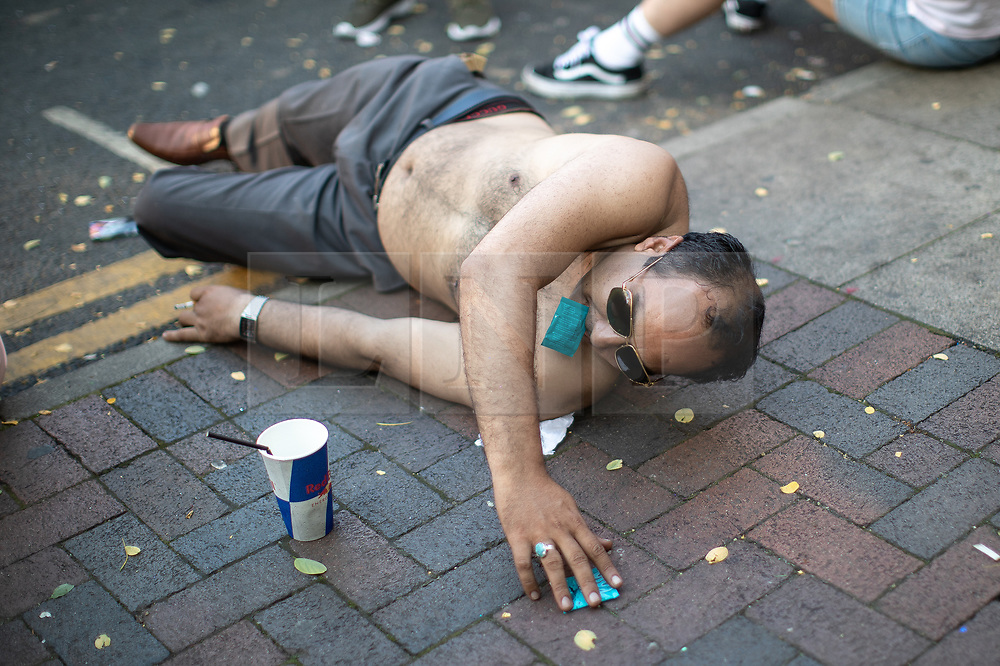 © Licensed to London News Pictures . 25/08/2019. Manchester, UK. A man lies on the ground with a condom in his mouth as he reaches out for another condom on the pavement . Revellers in Manchester's Gay Village during the city's annual Gay Pride festival , which celebrates LGBTQ+ life and is the largest of its type in Europe . Photo credit: Joel Goodman/LNP