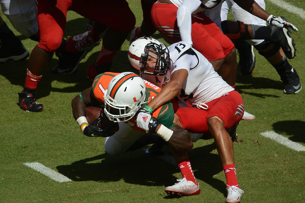 October 11, 2014: Grant Coleman #13 of the Cincinnati Bearcats tackles Gus Edwards #7 of the Miami Hurricanes during the football game between the Cincinnati Bearcats and the Miami Hurricanes at Sun Life Stadium in Miami Gardens, FL. The Hurricanes defeated the Bearcats 55-34.